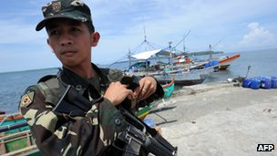 A Philippine soldier stands guard next to fishing boats at a pier in Masinloc town, Zambales province, 230km from Scarborough Shoal, 18 May 2012