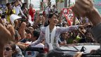 Burma's pro-democracy leader Aung San Suu Kyi waving