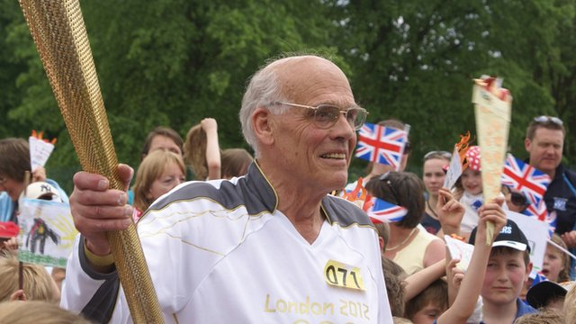 Torchbearer John Simpson carrying Olympic torch