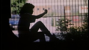 Silhouette of a girl looking through a park fence