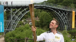 Torchbearer Lyndon Flavell holding the Olympic flame next to the Iron Bridge at Ironbridge Gorge