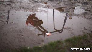 A child on a swing reflected in puddle