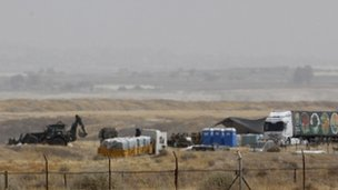 Israeli vehicles are seen near the border with Jordan as Israeli troops exhume the remains of Palestinians, May 2012