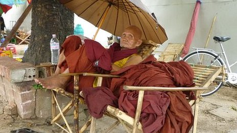 Elderly Burmese monk sits under sunshade