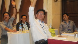 Malaysian businessmen raise hands at business conference in Rangoon