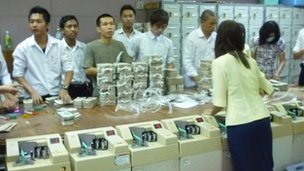 bank workers put piles of cash through mechanical counting machines inside Yoma Bank