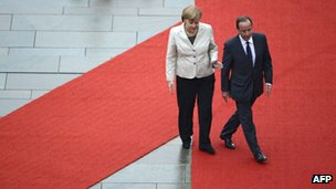German Chancellor Angela Merkel guides new French President Francois Hollande on the red carpet