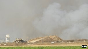 Smoke billows from the Gaza Strip as an Israeli tank monitors the border area after the firefight