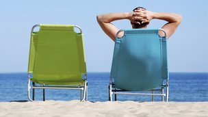Man reclining on a sun lounger on a beach