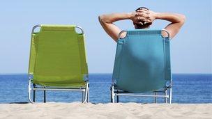 Man reclining on a sun lounger on a beach