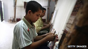 An Egyptian boy weaving a carpet