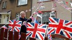 William Rattray puts up flags in his garden in Fallin, central Scotland, ahead of the Jubilee celebrations this weekend