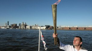 Craig Lundberg carries the Olympic flame on the Mersey Ferry