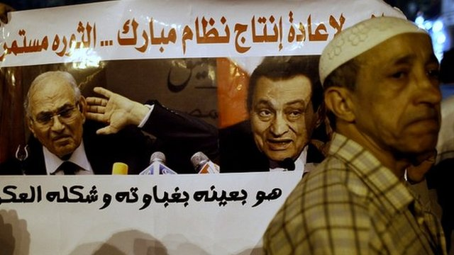 Man in front of Hosni Mubarak poster at Tahrir Square in Cairo in 1 June 2012