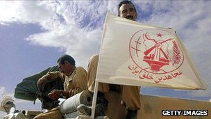 An MEK member displays the group's flag