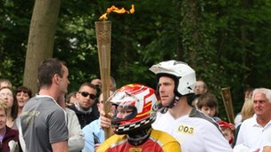 Torchbearer carrying Olympic flame whilst riding on back of motorbike