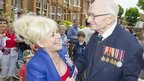 Barbara Windsor laughing with a war veteran at a street party