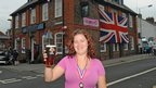 Landlady Kelly Bailey raises a pint of beer outside her pub The Jubilee