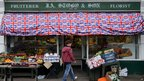 A woman walks into a fruit and vegetable shop as a canopy of Union flags hangs overhead.