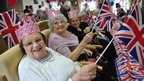 Ladies in hats smiling and waving flags. Photo: Lawrence Purcell