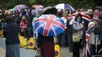 People queue with umbrellas to enter Battersea Park
