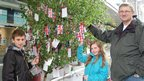 Lewis James, 12, Emma James, nine, and Mark James, from Tarleton, Lancashire, add their wishes for the Queen to Liverpool's Diamond Jubilee Wishing Tree