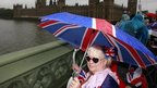 Sue Ridley waits on Westminster Bridge for the Royal Barge to pass the House of Commons and the Big Ben clock tower 