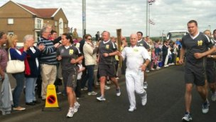 Michael Cole carries the torch in Portrush