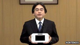 Satoru Iwata holding the Wii U gamepad