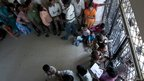 People queue up at a unique identification number enrolment booth in Delhi