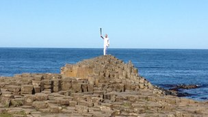 Peter Jack holds the flame aloft on the Giant&#039;s Causeway
