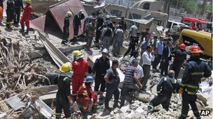 Firefighters and rescuers at the site of a bomb attack in the central Bab al-Muadham area in Baghdad, Iraq