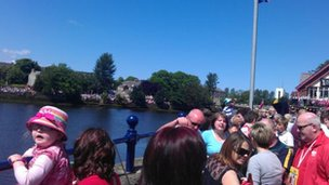 Crowds await the Olympic torch along the River Bann