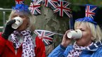Two women warm themselves with a hot drink as they wait for the beginning of a concert at Buckingham Palace to help celebrate the Diamond Jubilee of Queen Elizabeth II in London.