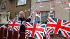 William Rattray putting up flags in his garden in Fallin, Central Scotland