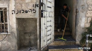 "A man clears debris from the entrance to a flat in Jerusalem following a suspected arson attack. The grafitti says: ""Get out of the neighbourhood"" (4 June 2012)"