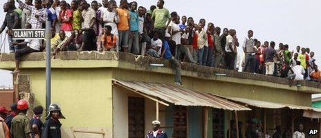People stand on top of a house viewing the site of a plane crash in Lagos, Nigeria, Monday 4 June 2012