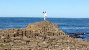 Peter Jack holding the torch aloft on the Giant's Causeway