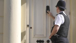 A policeman knocking on a door