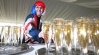A woman takes her glass of free champagne during special picnic in the grounds of Buckingham Palace