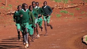 A photo of school children in Iten, where Abel Kirui trains, running around an athletics track after some full-time Kenyan athletes