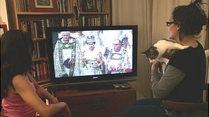 Two French people sit in front of a TV showing archive footage of the Queen