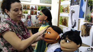A woman puts the finishing touches to some of Pakistan's Sesame Street characters