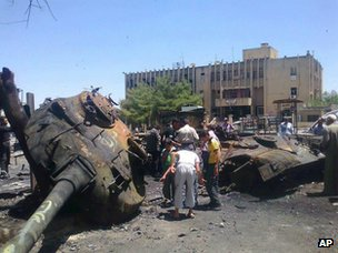 Locals inspect the remains of a destroyed Syrian army tank in the town of Ariha (4 June 2012)