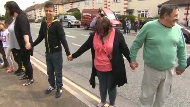 Residents hold hands outside house on Victory Road