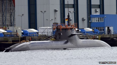 A Dolphin-class submarine anchors in front of docks of the Howaldts-Deutsche Werft (HDW) shipyard on Tuesday in Kiel, Germany