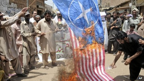 Pakistani protesters burn representations of US and NATO flags during a demonstration to condemn U.S. drone strikes in the tribal areas