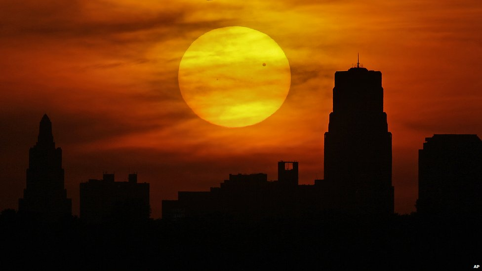 Venus is silhouetted as it crosses in front of the sun as it sets behind the Kansas City, Mo