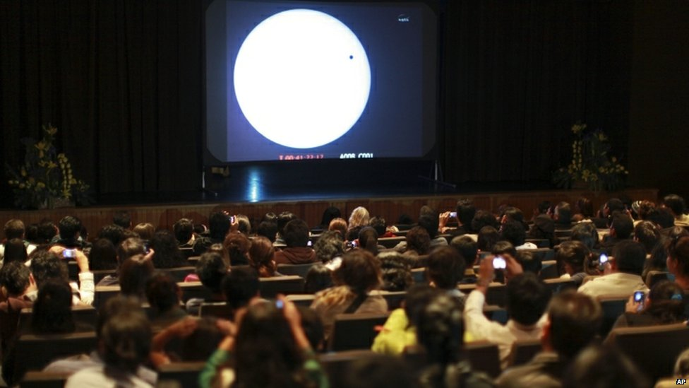 People watch a live webcast from the summit of Mauna Kea, Hawaii during the transit of Venus across the Sun at the auditorium of the Universum Museum in the National University (UNAM) in Mexico City, Mexico