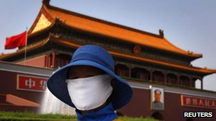 A cleaner wears a face mask as she works in front of Tiananmen Gate in Beijing